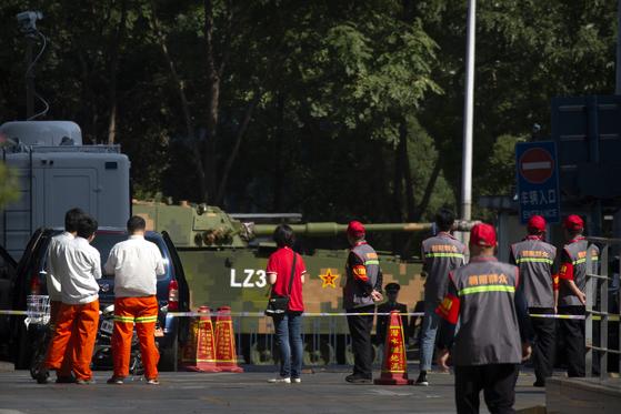 21일 열병식 리허설을 위해 도심을 지나는 인민해방군 탱크를 베이징 시민 조직인 '차오양 군중' 조끼를 입은 지원자들이 지켜보고 있다. 베이징시는 국경절 행사 보안을 위해 13만명에 이르는 차오양 군중 등 민간 조직을 총동원했다. [AP=연합]