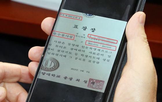 지난 6일 서울 여의도 국회에서 열린 법사위 조국 법무부 장관 후보자 인사청문회에서 박지원 의원이 휴대폰으로 전송된 조국 딸의 동양대학교 표창장을 보고 있다. [뉴시스]
