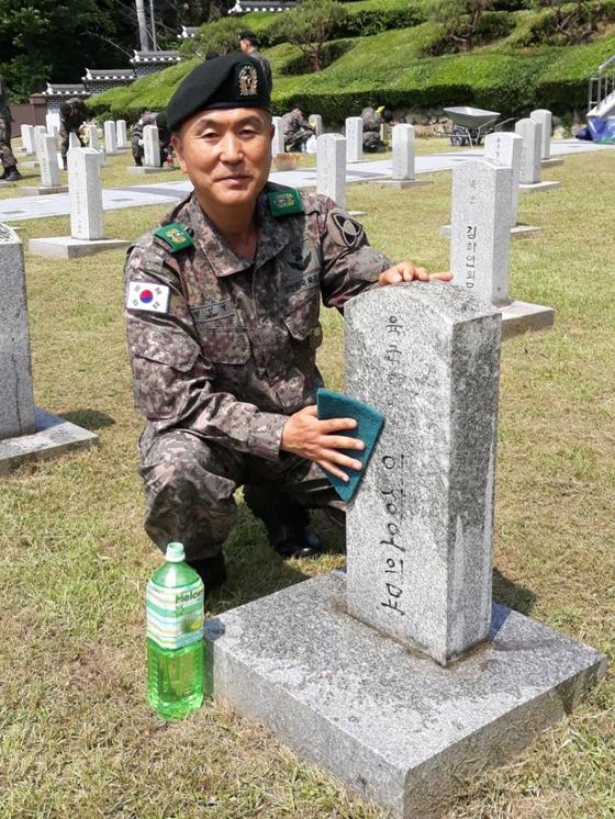전인석(55) 육군 35사단 전주대대 전주시 완산구지역대장이 지난달 27일 전주시 완산구 교동 군경묘지를 찾아 6·25 전쟁에 참전해 전사한 고(故) 이점수(아명 이상오) 하사의 묘비를 닦고 있다. [사진 육군 35사단]