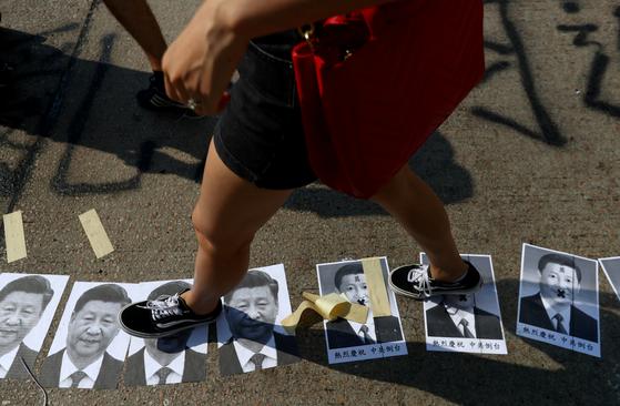 홍콩 시위대가 1일 시진핑 주석의 얼굴 포스터를 길바닥에 붙인 뒤 이를 밟고 지나가고 있다. [로이터=연합]