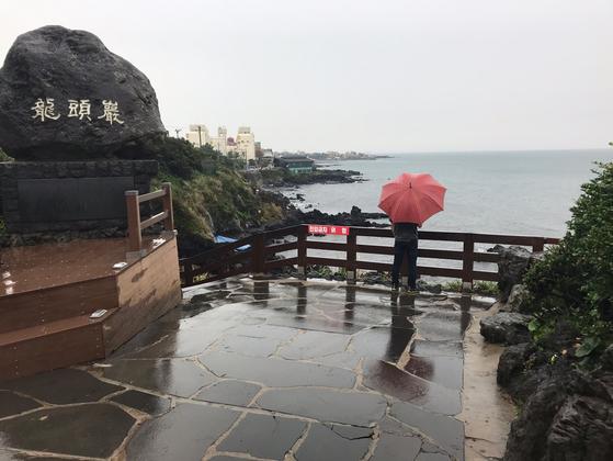 지난 1일 오후 제주의 대표 관광지 중 한곳인 용두암을 찾은 관광객이 우산을 쓴채 바다를 바라보고 있다. 최충일 기자
