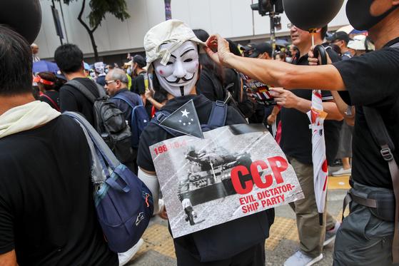 지난 1일 중국 국경절 당시 홍콩에서 열린 반중 시위에서 한 시위 참가자가 가이포크스 복면을 쓴 채 천안문 사태를 상징하는 탱크맨 사진을 들고 시위에 나서고 있다.[EPA=연합뉴스]