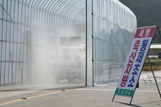 4일 오전 충남 홍성군 은하면의 거점소독시설에서 아프리카돼지열병(ASF) 확산을 막기 위한 차량 소독이 진행되고 있다. [연합뉴스]
