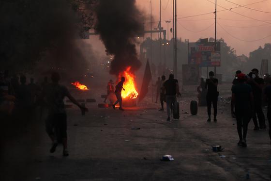5일 반정부시위대가 바그다드 시내 도로에 불을 질렀다. 이라크 경비대가 발포한 실탄에 수십 명의 시위대가 사망했다. [AP=연합]