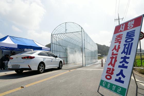 지난 4일 충남 홍성군 은하면의 거점소독시설에서 아프리카돼지열병(ASF) 확산을 막기 위한 차량 소독이 진행되고 있다. [연합뉴스]