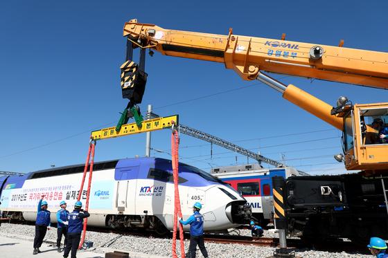 28일 강원도 강릉차량사업소에서 '2019 국가위기대응연습 고속철도 대형사고 실제 훈련'이 진행됐다. 코레일 관계자들이 열차가 탈선한 상황을 가정해 복구작업 훈련을 하고 있다. [뉴스1]