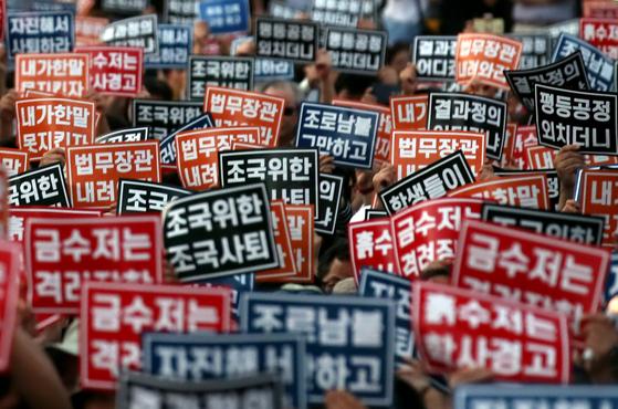 전국대학생연합 주최로 3일 오후 서울 종로구 대학로 마로니에공원 앞에서 열린 조국 법무장관 사퇴 촉구 촛불집회 참가자들이 LED 촛불과 함께 손팻말을 들어보이고 있다. [연합뉴스]
