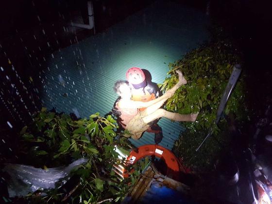 3일 새벽 제18호 태풍 '미탁'으로 400㎜가 넘는 폭우가 쏟아진 강원 삼척시 원덕읍 갈남리 한 주택에서 소방대원이 고립된 주민을 구조하고 있다. [연합뉴스]