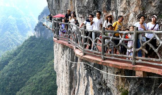 5일 중국 귀주성 완산지역 폐광 마을을 찾은 관광객들이 아찔한 수직 절벽길을 걷고 있다.[신화통신]