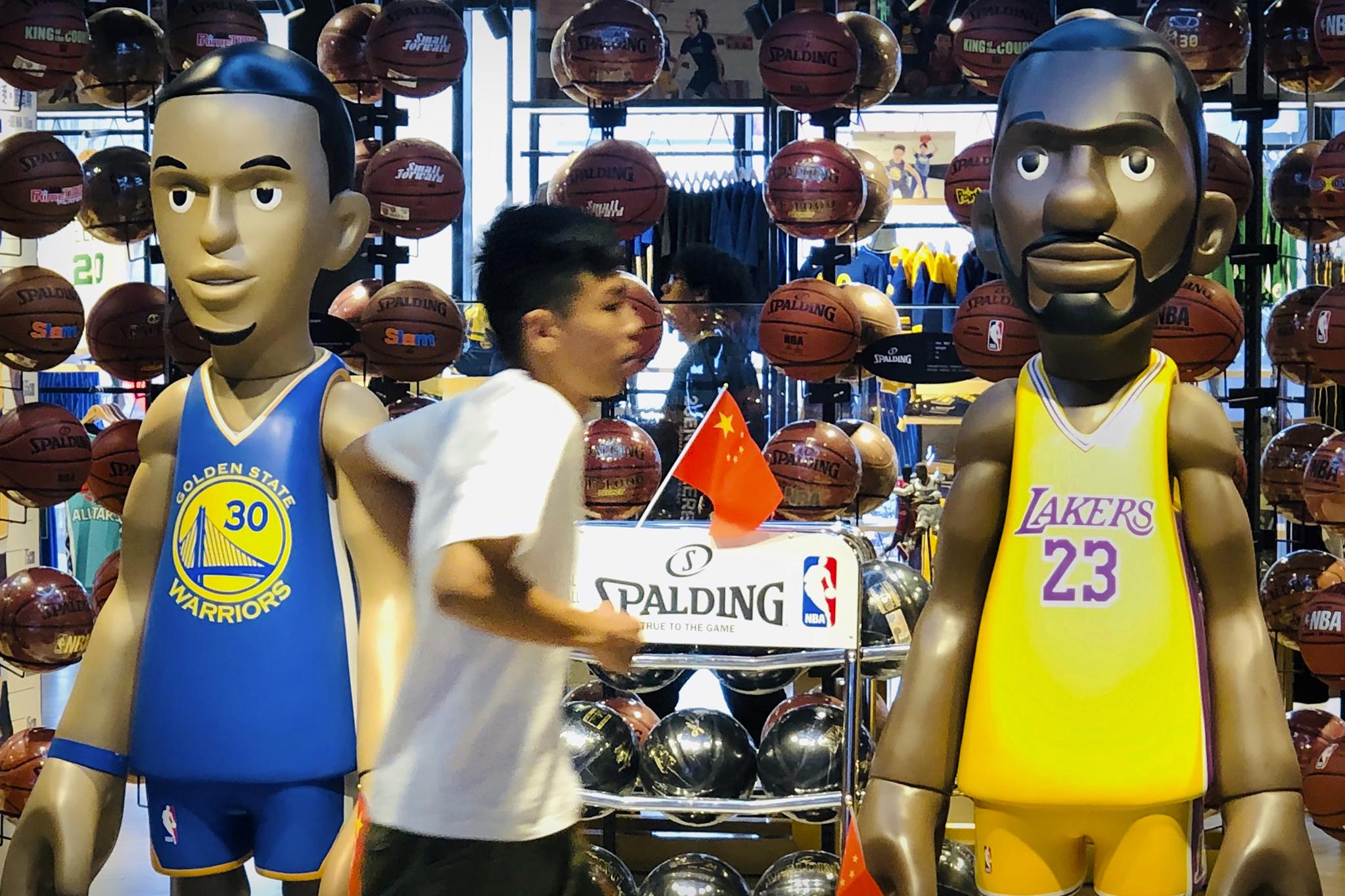 중국의 한 남성이 베이징에서 NBA 상품을 파는 가게를 지나가고 있다. 중국 CCTV는 8일 더 이상 NBA 픠시즌 경기를 중계하지 않는다고 밝혔다. [AP=연합뉴스]