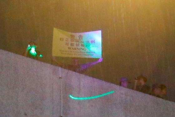 홍콩 시위대가 6일 까우룽통 중국 인민해방군 주둔지에 레이저 비추자 한 군인이 경고 문구가 쓰인 천을 들어 보이고 있다. [로이터=연합뉴스]