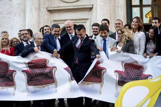 집권 오성운동을 이끄는 루이지 디 마이오 이탈리아 외무장관(갸운데)이 의원 수를 대폭 줄이는 법안이 하원을 통과한 후 의자가 그려진 현수막을 찢는 행사를 하고 있다. [AP=연합뉴스]