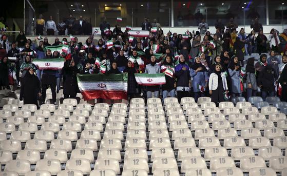 이란 여성축구팬들이 작년 10월16일 아자디경기장에서 열린 이란과 볼리비아의 남자축구 경기를 응원하고 있다. 앞쪽으로 남녀 공간을 분리하기 위해 비워둔 좌석이 보인다. [AP=연합뉴스]