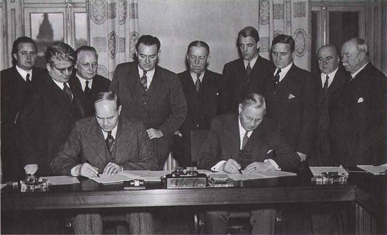 1938년 12월 20일 스웨덴 스톡홀름 동쪽의 휴양지 살트셰바덴에서 어거스트 린드베리 스웨덴 전국생산직노조(LO) 위원장(왼쪽)과 지그프리트 에드스트룀 사용자대표(SAF)측 대표가 합의문에 서명하고 있다. [위키피디아]