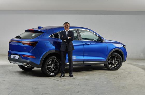 이강수 신원CK모터스 대표가 10일 출시한 크로스오버차량 '펜곤 ix5' 앞에서 포즈를 취하고 있다. 쿠페형 SUV 디자인은 BMW 출신 디자이너의 작품이다. [사진 신원CK모터스]