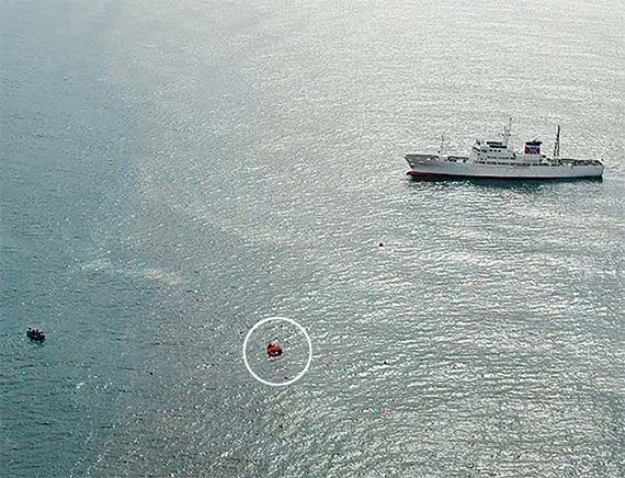 지난 7일 동해상에서 북한 어선과 일본 어업 단속선(오른쪽)이 충돌해 북한 어선이 침몰했다. 사고 직후 일본 구조 배·헬기 등이 투입돼 구명보트(흰색 동그라미)에 탄 북한 선원 20명을 포함 60여명을 모두 구조했다. [로이터=연합뉴스]