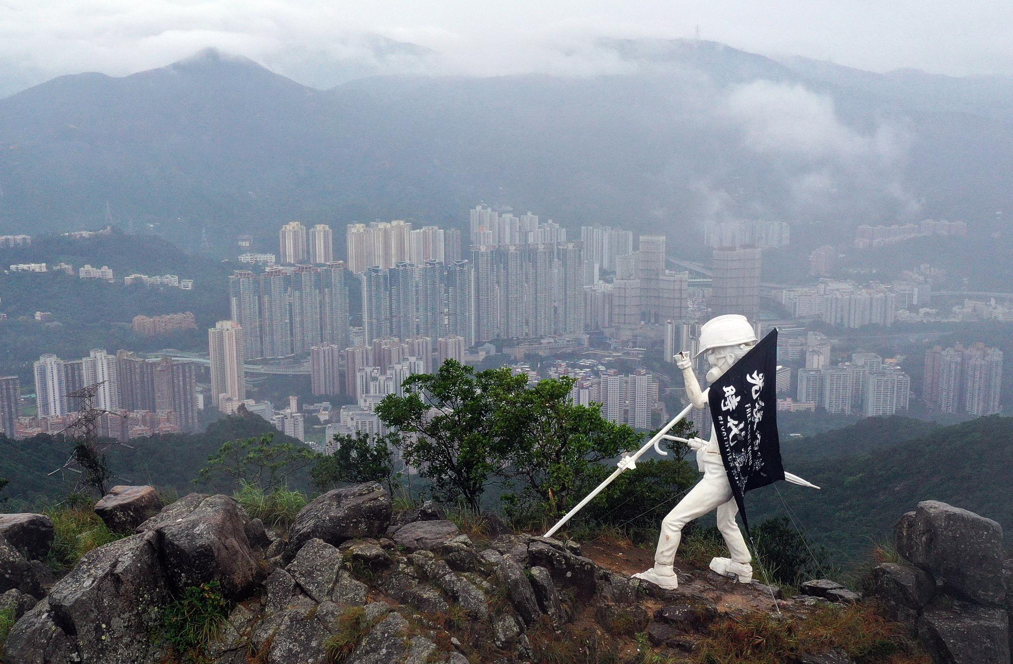 홍콩의 랜드마크인 사자산 정상에 13일 자유의 여신상이 설치됐다. '홍콩해방, 시대혁명'이라고 적은 깃발을 들고 있다. [ EPA=연합뉴스]