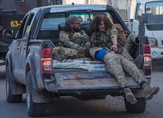 터키의 지원을 받는 시리아 반군 군인들이 12일 부상을 입고 픽업 트럭에 실려 국경지역인 텔아비아드로 돌아가고 있다. [AP=연합뉴스]