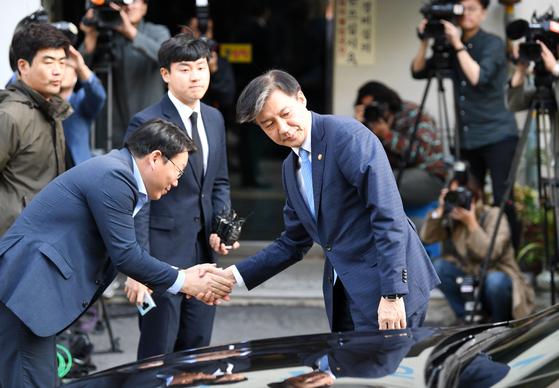 """사의를 표명한 조국 법무부 장관이 14일 오후 경기도 과천시 법무부 청사를 떠나 서울 서초구 방배동 자택에 들어서며 관계자들과 악수를 하고 있다.  조 장관은 이날 '검찰개혁을 위한 '불쏘시개' 역할은 여기까지입니다'는 자료를 내고 '오늘 법무부 장관직을 내려놓는다""""고 밝혔다. [뉴스1]"""