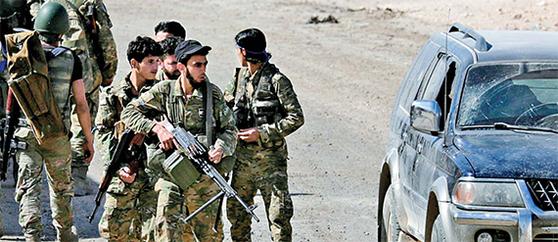 쿠르드족이 통제하는 시리아 북부에 대한 터키의 공습이 시작된 지 나흘째인 12일(현지시간) 친터키 성향의 시리아 반군들이 터키 접경도시인 텔아비야드에서 무장한 채 이동하고 있다. 이날 터키 국방부는 시리아 내 쿠르드 요충지인 라스알아인 시를 통제하고 있다고 밝혔다. [로이터=연합뉴스]