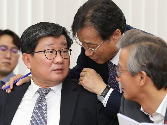 더불어민주당 전해철(왼쪽) 의원이 15일 오전 서울 여의도 국회 정무위원회에서 열린 한국자산관리공사 한국주택금융공사 신용보증기금 한국예탁결제원 국정감사에서 유동수(가운데) 민주당 간사와 이야기를 나누고 있다. 오른쪽은 전재수 더불어민주당 의원. [뉴시스]
