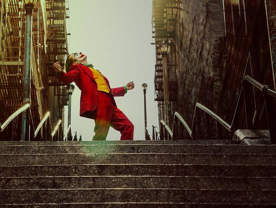 15일 개봉 2주 만에 400만 관객을 돌파한 영화 '조커'. 사진은 주연 호아킨 피닉스의 열연으로 회자되는 장면으로, 광대 아서 플렉이 자유롭게 춤을 추며 계단을 내려오는 모습이다. [사진 워너브러더스 코리아]