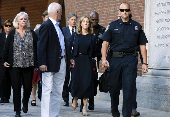 할리우드 유명 여배우 펠리시티 허프만(가운데)이 지난 9월 13일 딸의 SAT 점수를 조작한 혐의로 선고를 앞두고 법원으로 들어가고 있다. [AP=연합뉴스]