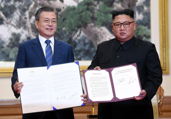 문재인 대통령과 김정은 국무위원장이 지난해 9월 19일 오전 평양 백화원 영빈관에서 평양공동선언문에 서명한 후 합의서를 들어보이고 있다. [뉴스1]