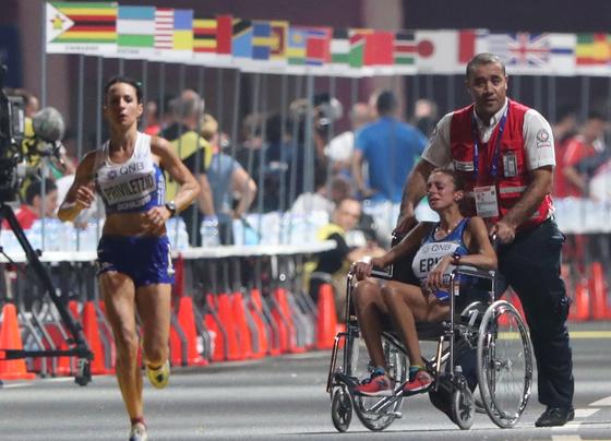 지난달 26일 카타르 도하에서 열린 세계육상선수권대회 여자마라톤 경기 도중 무더위로 경기를 포기항는 사례가 속출했다. 이날 경기서 기권한 이탈리아의 지오바나 에피스 선수가 휠체어를 타고 경기장 밖으로 나가며 울고 있다. [EPA=연합뉴스]