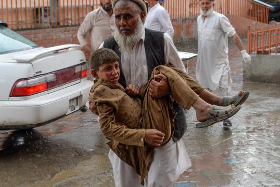 18일(현지시간) 아프가니스탄 동부 이슬람 사원에 폭탄 테러가 발생했다. 부상당한 어린이가 겁에 질려있다. [AFP=연합뉴스]