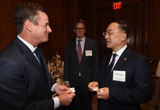 홍남기 부총리 겸 기획재정부 장관(오른쪽)이 16일(현지시간) 미국 뉴욕에서 열린 한국경제 설명회에 앞서 한 참석자와 대화를 나누고 있다. [뉴스1]
