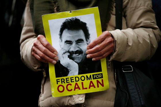 프랑스 스트라스부르의 유럽위원회 앞에서 지난 9일 터키의 시리아 쿠르드족 공격을 항의하는 시위에 참석한 사람이 쿠르드 노동자당(PKK) 지도자 압둘라 오잘란의 사진을 들고 있다.사진에는 그의 석방을 요구하는 구호이자 단체 이름이 영문으로 적혀 있다. [로이터=연합뉴스]