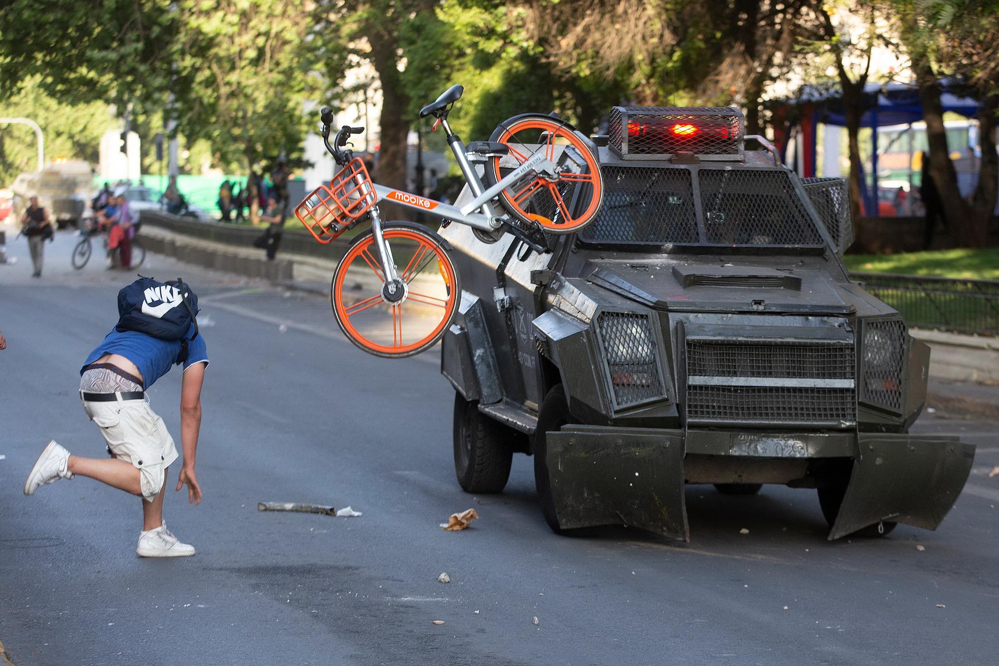 칠레 수도 산티아고에서 지하철 요금 인상에 반대하는 시위가 격렬하게 벌어지고 있다. 한 시위대가 경찰 최루탄 발사차량을 향해 자전거를 던지고 있다. [AFP=연합뉴스]