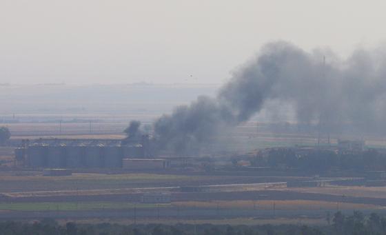 18일 터키군의 폭격을 받은 시리아 라스알아인 지역에서 연기가 피어오르고 있다. [로이터=연합뉴스]