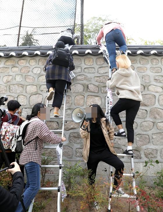 한국대학생진보연합이 18일 오후 서울 중구 주한 미국대사관저에서 방위비분담금 협상과 관련해 기습 농성을 하기 위해 담벼락을 넘고 있다. [뉴시스]