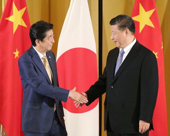 지난 6월 27일 아베 신조 일본 총리(왼쪽)와 시진핑 중국 국가주석이 일본 오사카의 한 호텔에서 정상회담에 앞서 악수를 나누고 있다. [교도=연합뉴스]