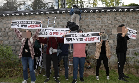 한국대학생진보연합 소속 대학생이 지난 18일 오후 서울 중구 주한 미국대사관저에서 방위비분담금 협상 관련 기습 농성을 하기 위해 담벼락을 넘고 있다. [뉴시스]