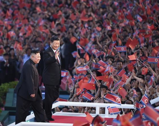 시진핑 중국 국가주석이 지난 6월 20일 북한 5.1 경기장에 운집한 10만 평양 시민에 손을 들어 인사하고 있다. 시 주석 뒤를 따르는 김정은 북한 국무위원장의 발걸음은 '시 주석 띄우기'의 대표적 모습이다. [AP=연합뉴스]