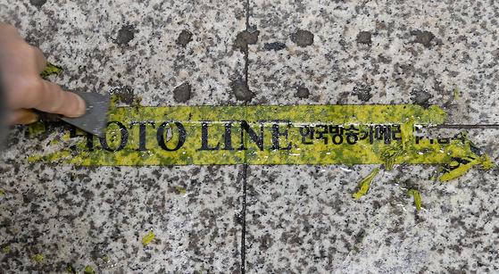 지난 8일 조 전 장관의 동생 조모씨의 영장심사 출석을 앞두고 서울중앙지방법원에 설치됐던 포토라인의 모습. 조씨가 영장심사 출석을 포기하자 법원 관계자가 법원 출입구에 표시된 '포토라인'을 제거하고 있다. [뉴스1]