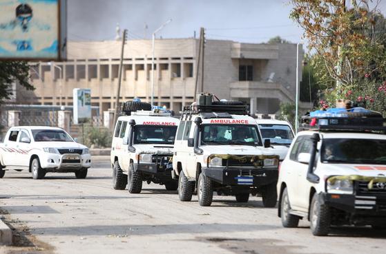20일(현지시간) 터키와 인접한 시리아 북동부 도시 라스 알 아인에서 시리아민주군(SDF) 소속 부상병을 실은 구급차들이 도시를 빠져 나가고 있다.[AFP=연합뉴스]