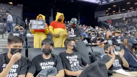 농구경기 도중 곰돌이 푸 복장을 하거나 홍콩 지지 문구가 써진 티셔츠를 입고 시위를 벌이는 관중들. [로이터=연합뉴스]