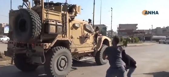 시리아 북동부 알 하사카 지방을 떠나는 미군 차량을 향해 주민들이 돌, 음식물을 던지며 항의하고 있다. [유튜브 캡처]