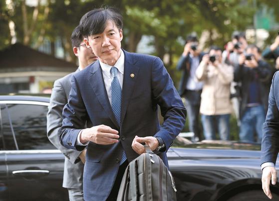 전격적으로 사의를 밝힌 조국 법무부 장관이 지난 14일 오후 법무부 관계자로부터 가방을 받아들고 방배동 자택으로 들어가고 있다. [연합뉴스]