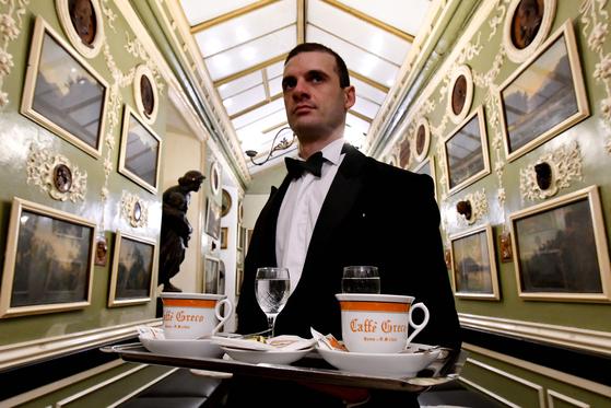 나비 넥타이를 한 카페 그레코의 웨이터가 2018년 1월 손님에게 커피를 서비스하고 있다. [AFP=연합뉴스]
