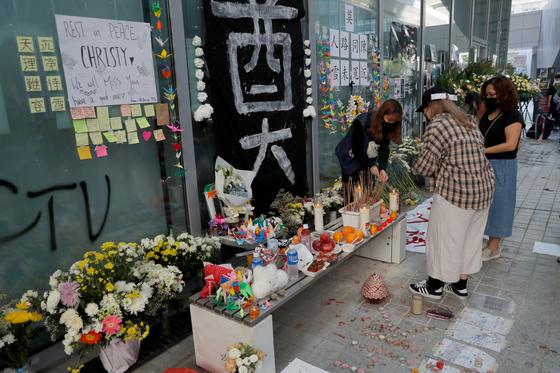 지난 17일 홍콩 티우켕렝(調景嶺)에 마련된 추모공간에서 시위대가 극단적 선택을 한 동료를 위해 촛불을 밝히고 있다. [로이터=연합뉴스]