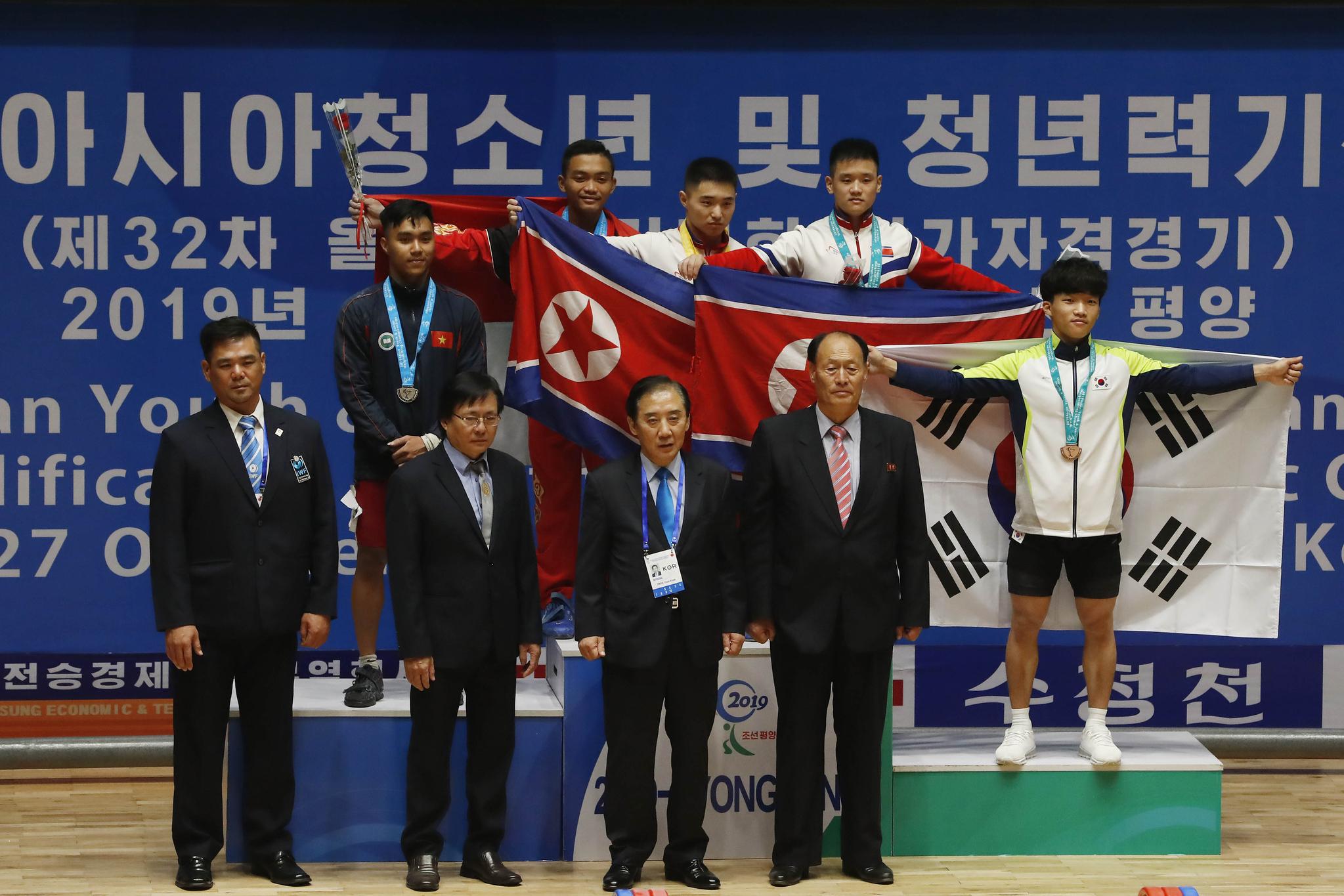 2019 아시아 유소년·주니어 역도선수권대회가 열리고 있는 22일 평양 청춘가역도경기장에서 남자 주니어 61kg급 용상 3위를 기록한 한국 배문수(뒷줄 오른쪽부터)가 북한의 오원관(종합3위), 김충국(종합1위)을 비롯한 수상 선수들과 시상대에 올라 기념사진을 찍고 있다. [사진공동취재단]