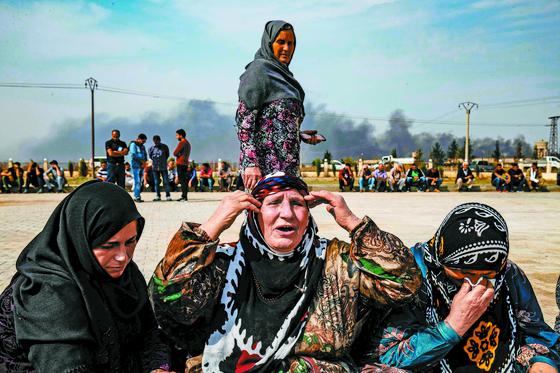 전통 의상 차림의 쿠르드족 여성들이 시리아 주둔 미군이 철수한 뒤 벌어진 터키군의 공격을 받아 숨진 친지들의 장례식에 참석해 비통한 표정을 짓고 있다. [라스알린 AFP=연합뉴스]