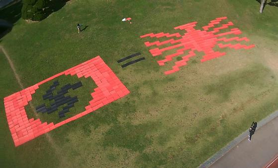 지난 9일 전남대학교 윤동현 학생이 전대 운동장에 일본 군국주의를 상징하는 욱일기는 독일 나치즘을 상징하는 나치기(하켄크로이츠)와 같다는 의미의 대형 아트퍼포먼스를 펼치고 있다. [뉴스1]