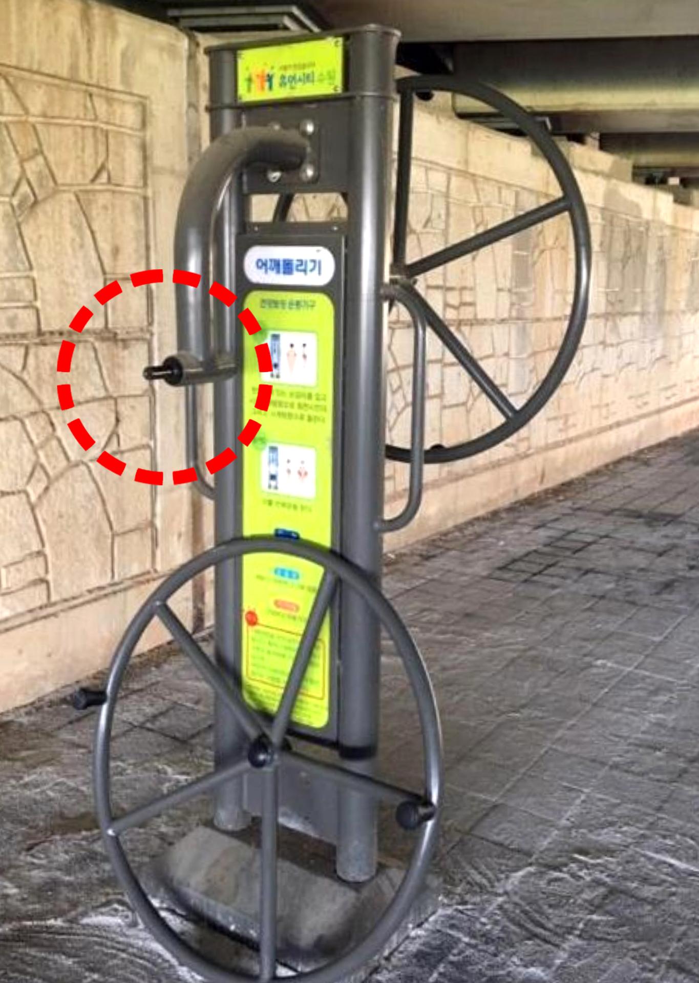 공공 운동기구 '어깨돌리기'에서 원형 바퀴가 분리된 모습. 손잡이가 달려있는 원형 바퀴의 볼트가 본체와 연결이 느슨하게 돼 있었던 것으로 조사됐다. 이 운동기구엔 '휴먼시티 수원'이라고 표시돼있다. [사진 인터넷 카페]