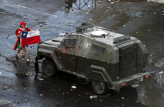 22일(현지시간) 한 시위자가 칠레 국기를 들고 장갑차를 막아서고 있다. [AP=연합뉴스]